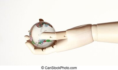 wooden hand of mannikin holding globe, rotating on white...