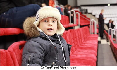 boy sits in armchair, attentively watch hockey match, then...