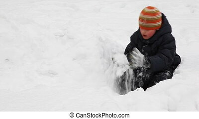 boy sits among snow and builds of it wall in winter frosty...