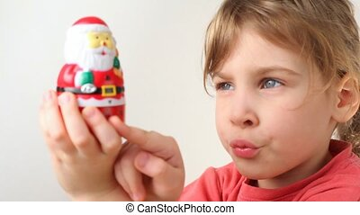 girl with kitchen timer in Santa Claus form - little girl...