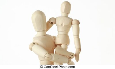 wooden figures of child sitting on hands of his parent