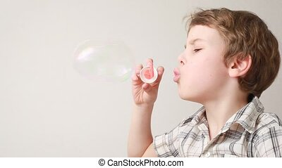 boy blowing soap bubbles on white background, profile