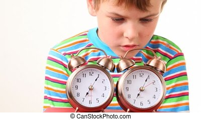 boy shut off pair of ringing alarm clocks on white...