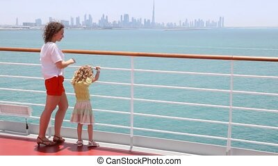 woman and girl are standing at railing on deck, back view