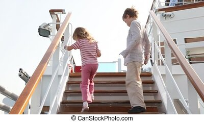 children are going up ladder on deck of ship and...