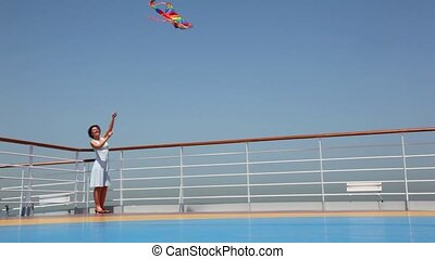 general view on woman flying kite on deck - general view on...
