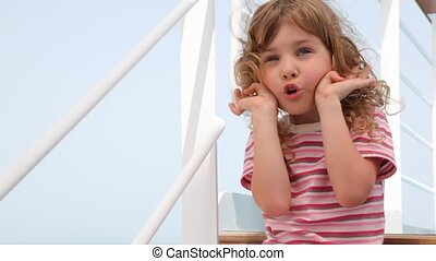 girl is making faces on deck of ship - little girl is making...