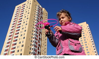 girl runs toy helicopter against backdrop of high-rise...