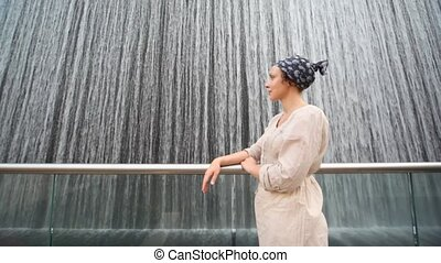 woman is standing at waterfall