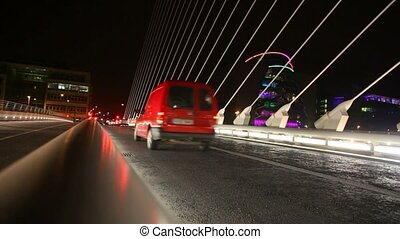 cars moving on Samuel Beckett Bridge, night illumination on...
