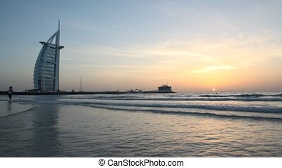 girl running on the surf during sunset near the Burj Al Arab...