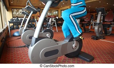 legs of woman training on exercise bicycle in fitness center
