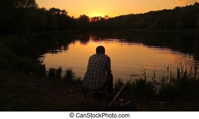 back view of fisherman sitting near pond in park during...