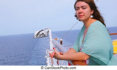 woman is standing on deck - Young beautiful woman is...