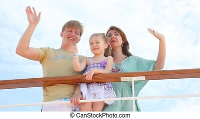 family standing on the ship is waving hands