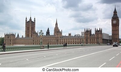 People and cars moving on Westminster Bridge, Big Ben in...