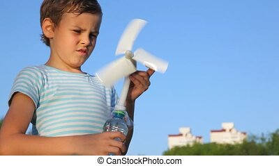 boy holding toy wind-driven generator in his hands