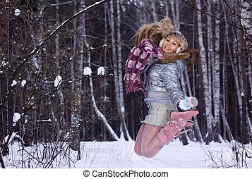 smiling young woman jumping in winter forest