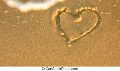 sea wave erases drawing hearts with sand