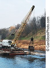 Deepening of the river by a dredge