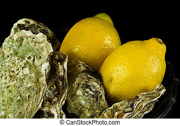 Oysters and lemons in a basket on black background