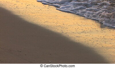 Gentle waves on a sandy beach in sunrise, closeup, Canon XH...