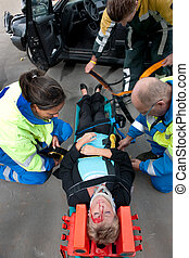 First aid - Paramedics and a fireman strapping an injured...