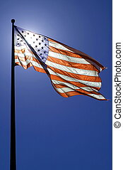 waving american flag, clear blue sky, sun is directly behind...