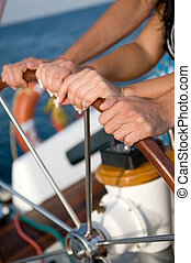 helm yacht - the hands of men and women run the helm yacht