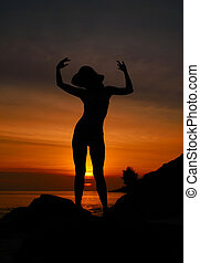 Sunset Woman Silhouette - A colourful sunset image with a...
