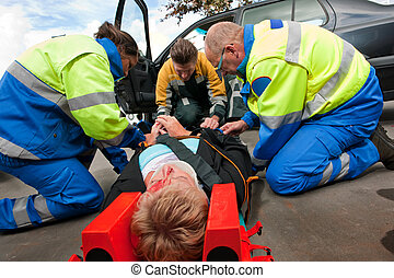First aid Teamwork - Two paramedics and a fireman working...