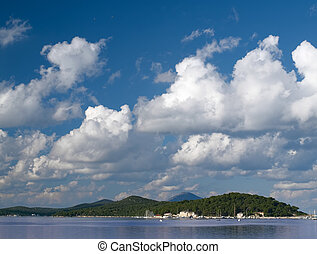 Adriatic coast with white scattered clouds and blue sky,...