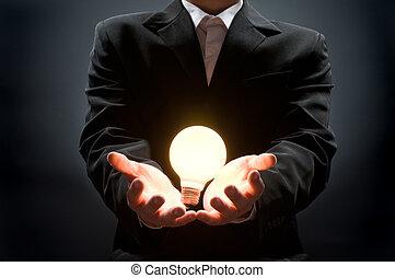 illuminated bulb - a man pointing to the illuminated bulb