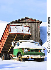 Old Farm Truck in Winter - Old farm truck parked in front of...