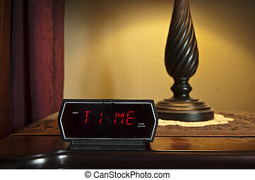 Time - A digital alarm clock displaying the word Time on the...