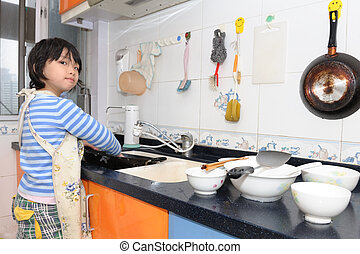 Asian kid washing dishes - Asian kid washing the dishes in...