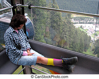 woman sitting on the cabin of a cable car as it climbs the...