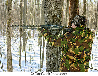 camouflaged hunter in winter woods