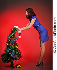 beautiful girl decorating christmas tree, red background