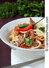 Stirfried beef with  chili peppers in a white cup