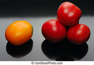 Multicolored tomatoes on a black backgrouns - Red and yellow...
