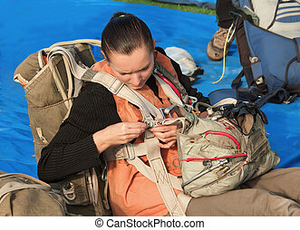 The young parachutist dresses a parachute sitting on the...