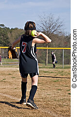 Young Girl Throwing Softball - A preteen girl throwing a...