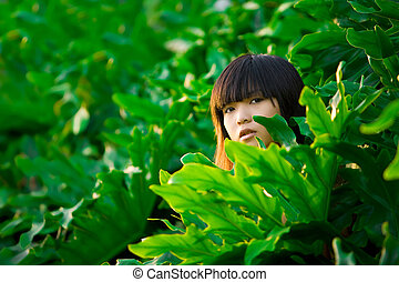 Curiosity - Asian girl peeks out from behind lush green...