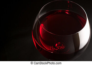 Red wine - Glass of red wine close-up on black background.