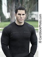 Portrait of young muscular man in black shirt outdoors
