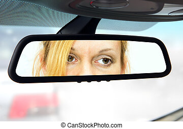 rear-view mirror - woman sits on driver's seat and Looks in...