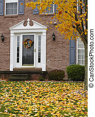 Inviting Home in Autumn - A brick home's front doorway with...