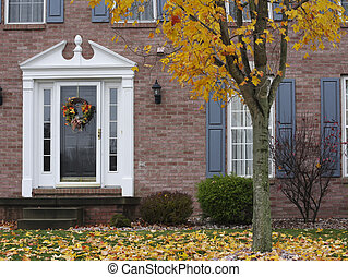 Inviting Autumn Home - A fall wreath hangs on the door of a...