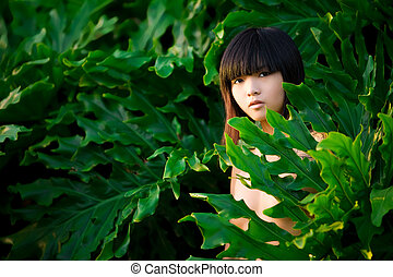 Natural beauty - Asian woman peeks out from behind lush...